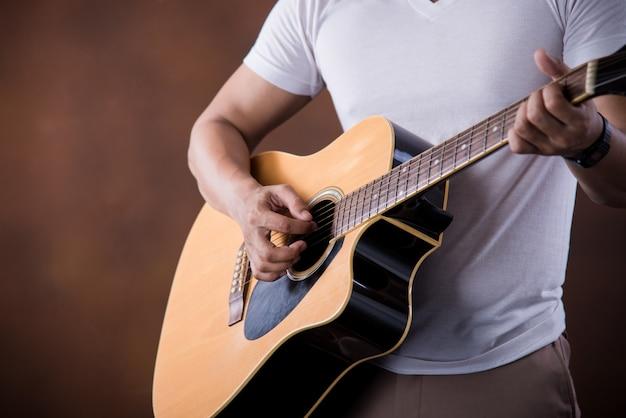 Азиатский молодой человек музыкант с акустической гитарой Бесплатные Фотографии