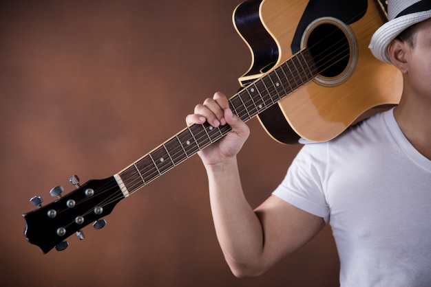 アコースティックギターとアジアの若い男ミュージシャン 無料写真