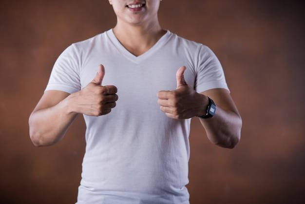 指を指して親指をあきらめて肖像ハンサムな若い笑みを浮かべて男 無料写真