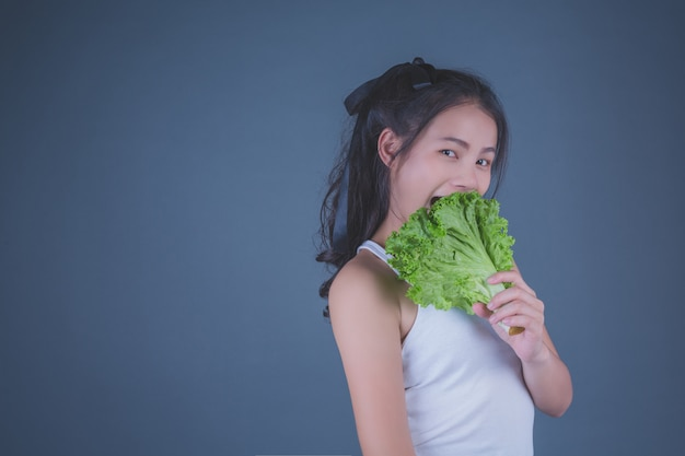 女の子は灰色の背景に野菜を保持します。 無料写真