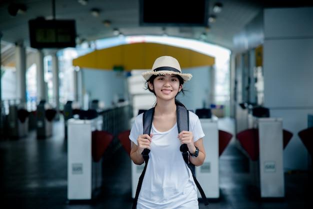 街背景でバックパックと幸せの笑みを浮かべてアジア学生少女 無料写真