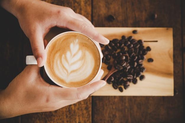 ウッドテクスチャ上の女性の手に一杯のコーヒー。 無料写真