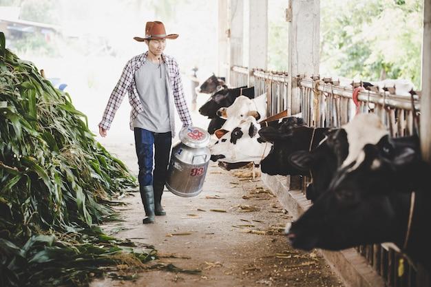 農村部のシーンで屋外ミルクコンテナーと一緒に歩いているハンサムなミルクマンの肖像画 無料写真