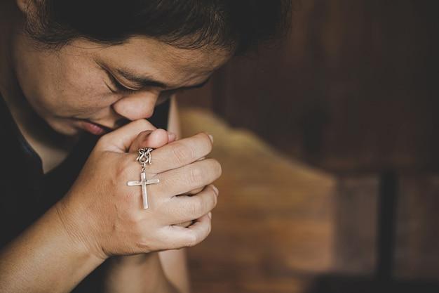 Крупный план христианской старшей женщины вручает держать распятый крест пока молящ бога. Бесплатные Фотографии
