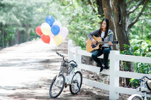 アコースティックギターに笑みを浮かべて美しいアジアの女性 無料写真