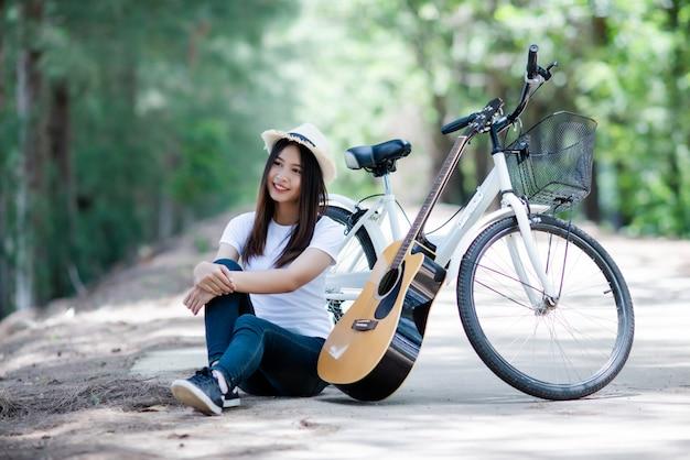 自然で自転車でギターを弾く美しい少女の肖像画 無料写真