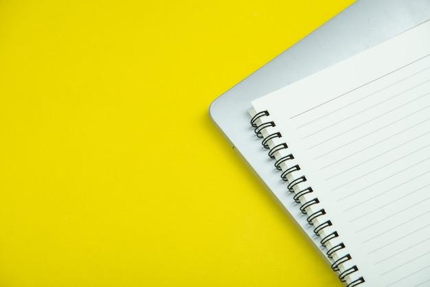 それにたくさんのものを持つ黄色のオフィスデスクテーブルの平面図です。 無料写真