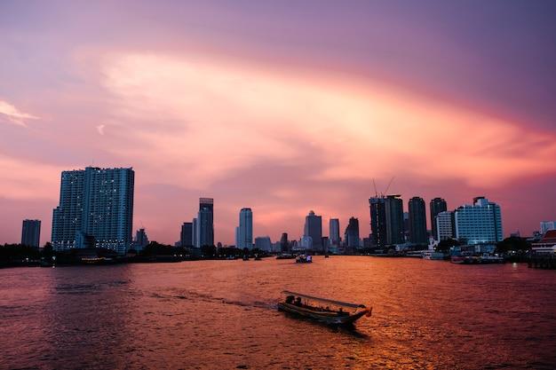 日没の川市とバンコクのバックグラウンドでフェリーボート 無料写真