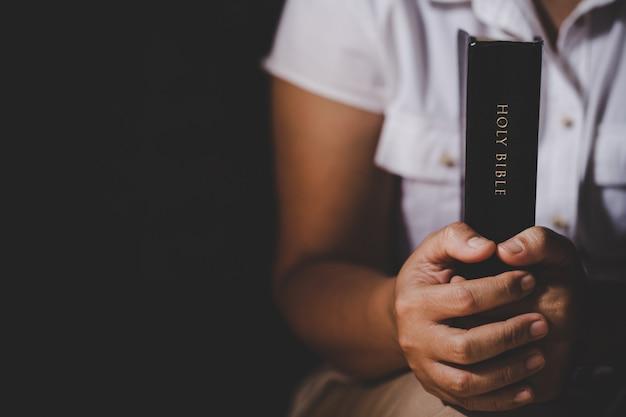 霊性と宗教、信仰のための教会の概念での聖書の祈りに手を組んだ。 無料写真