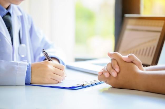 医師の男性が病院の机で申請書を記入しながら患者に相談します。 無料写真