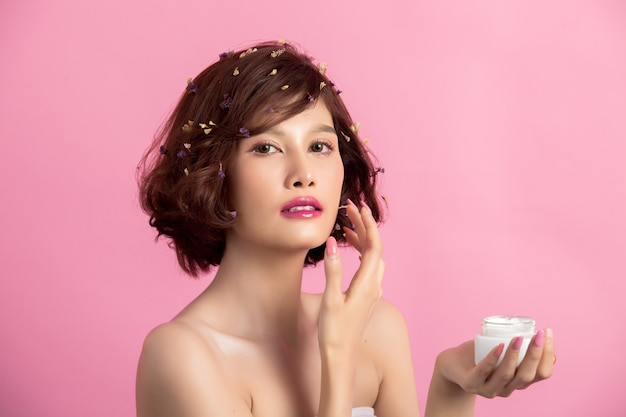 美しさの概念。女性は彼女の手で保湿剤を保持しています 無料写真