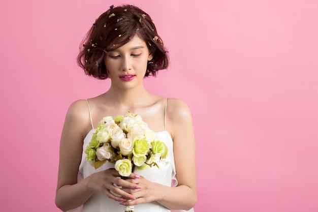 ピンクに分離された花を持って笑顔の遊び心のあるかわいい女の肖像 無料写真