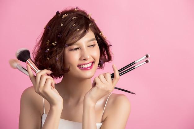 ショートヘアアジアの若い美しい女性の化粧品パウダーブラシを適用する 無料写真