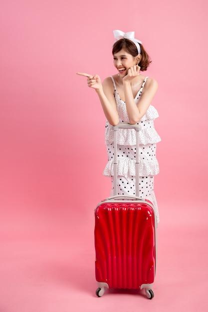 Путешественник туристическая женщина в летней повседневной одежде с чемоданом путешествия, изолированных на розовый Бесплатные Фотографии