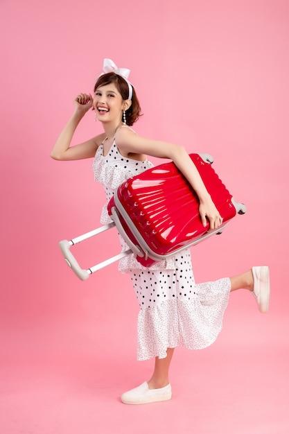 ピンクに分離された旅行スーツケースと夏のカジュアルな服装で旅行者観光客の女性 無料写真