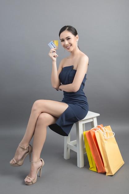 買い物袋とクレジットカードを手に持つ美しいアジアの女性 無料写真