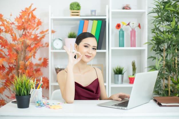 陽気なビジネス女性のオフィスでラップトップに取り組んで 無料写真