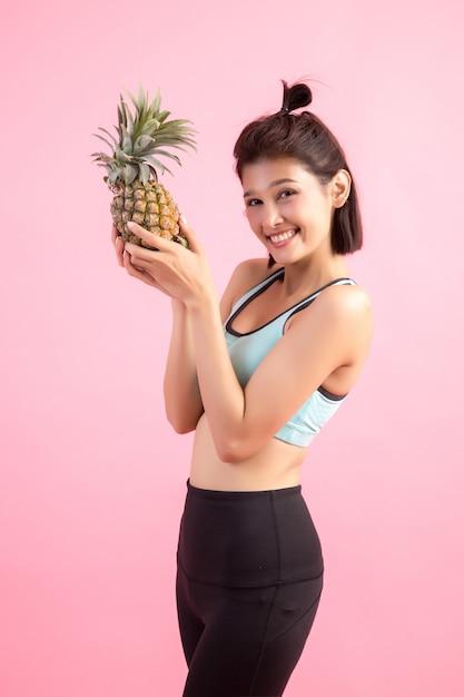 体重を制御する運動の後健康的でうれしそうな笑みを浮かべてパイナップルフルーツ女性 無料写真