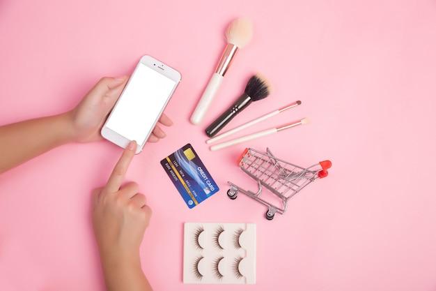 女性がスマートフォンやクレジットカードを使って美容アイテムをショッピング 無料写真