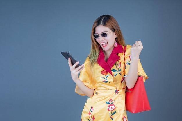 携帯電話とスマートカードを保持している女性。 無料写真