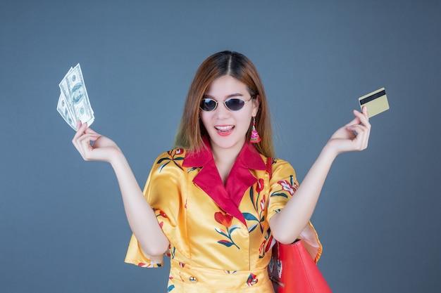パパ活、契約、お手当、出会い系、副業 お金とカードを持つ女性
