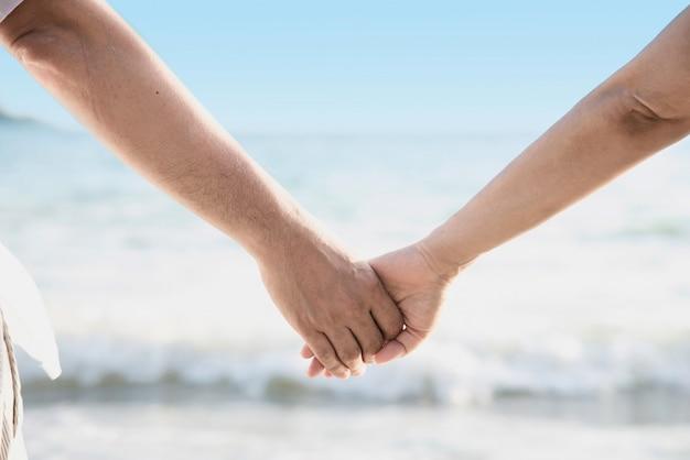 Азиатская пара держит руку рядом с морем Бесплатные Фотографии