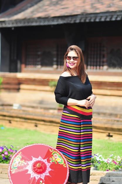 チェンマイランナータイの屋外観光地でカラフルな北部タイ風衣装で中年のタイ人女性 無料写真