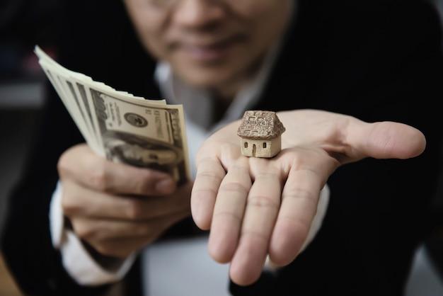 Деловой человек показать деньги банкнота сделать финансовый план пригласить людей, чтобы продать или купить дом и автомобиль Бесплатные Фотографии