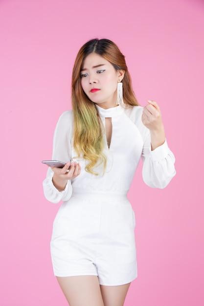 電話と顔の感情を見せて、白いドレスを着た美しい女性 無料写真