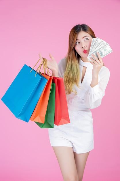 女の子はファッションの買い物袋を保持し、ドルカードを保持しています 無料写真