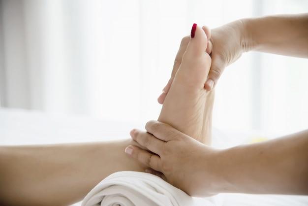 マッサージ師から足マッサージサービスを受ける女性を手と足でクローズアップ - 足マッサージ療法サービスコンセプトでリラックス 無料写真