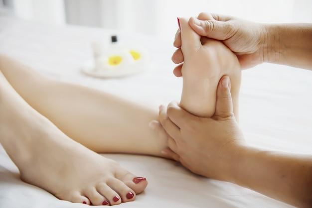 Женщина получает массаж ног от массажиста крупным планом под рукой и ногой - расслабиться в концепции обслуживания массаж массаж ног Бесплатные Фотографии