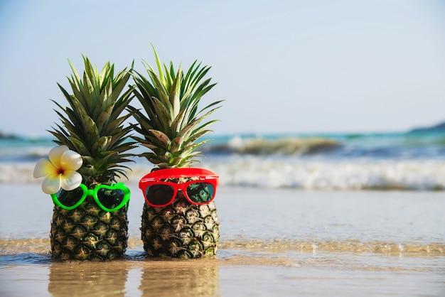 素敵なカップルの新鮮なパイナップルは海の波 - 海砂の太陽休暇の概念と新鮮な果物ときれいな砂のビーチに太陽の素敵なメガネを置く 無料写真