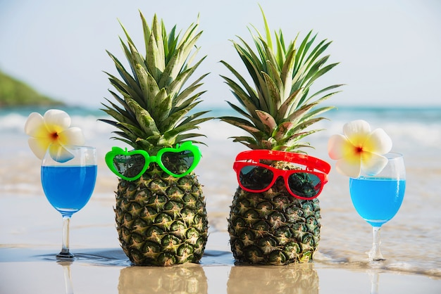 Свежие ананасы с солнцезащитными очками и коктейльными бокалами на чистом песчаном пляже с морской волной - свежие фрукты и напитки с концепцией отдыха на солнце с морским песком Бесплатные Фотографии