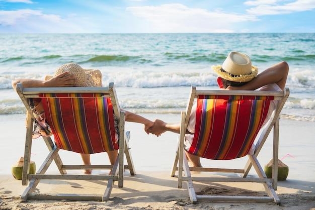 Расслабьтесь пара лежат на пляже чиар с морской волной - мужчина и женщина отдыхают на море природа концепция Бесплатные Фотографии