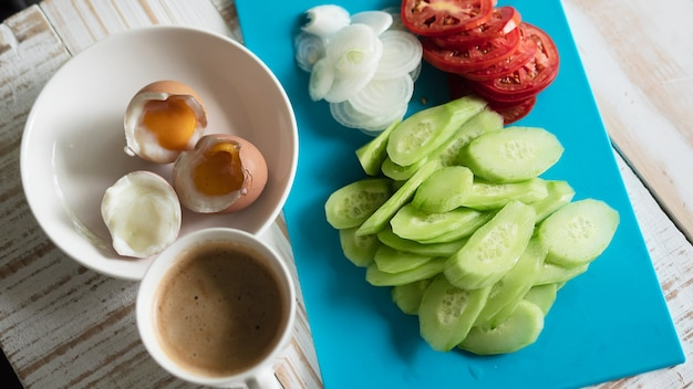 ゆで卵、新鮮なキュウリのサラダとコーヒーカップの朝食セット - トップビュー朝食食品のコンセプト 無料写真