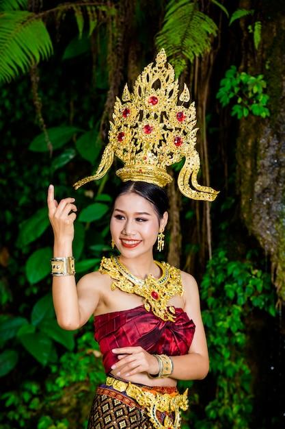 女性は滝に古代のタイのドレスを着ていました。 無料写真