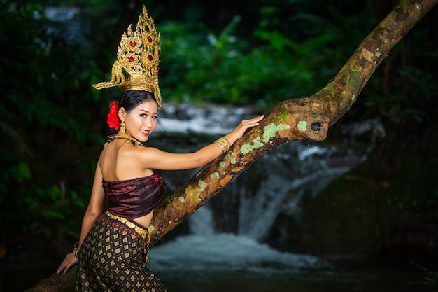 Женщина одета в старинное тайское платье у водопада. Бесплатные Фотографии