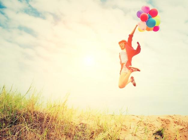 風船とビーチでジャンプガール 無料写真
