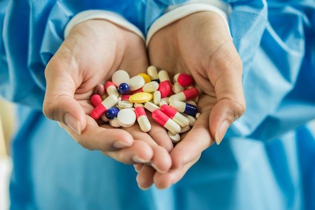 女性の手がボトルから薬の丸薬を注ぐ 無料写真