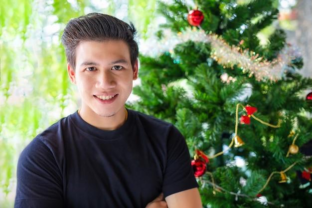 クリスマスツリーの肖像画ハンサムな男 無料写真