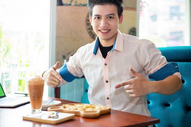 コーヒーショップでデザートを持つ若者 無料写真