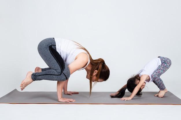 Молодая мама тренирует прекрасную дочь с йогой Бесплатные Фотографии