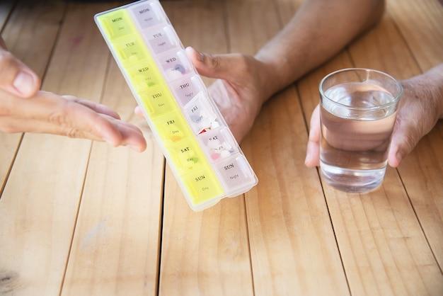 医師は、患者がピルボックスで錠剤を正しく食べるのを支援します 無料写真