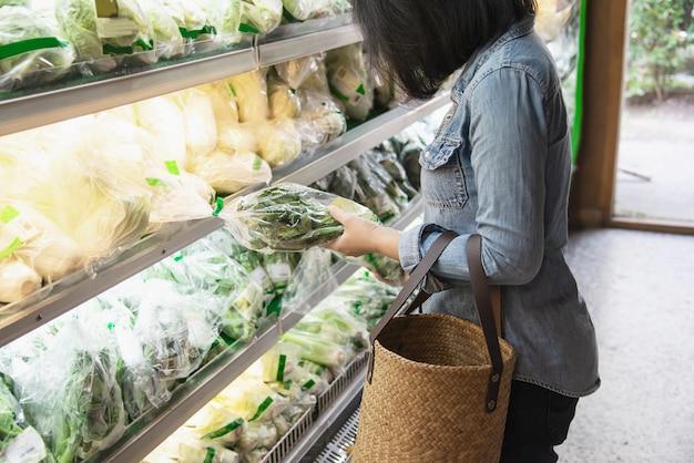 女性はスーパーマーケットで新鮮な野菜を買い物 無料写真