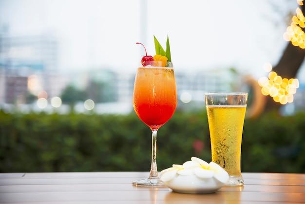 世界中のクールなビールとマイタイまたはマイタイのグラスは、夕暮れのカクテルを好む 無料写真