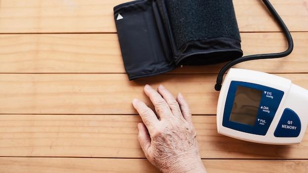 老婦人は血圧モニターの子供セットを使用して血圧をチェックされています 無料写真