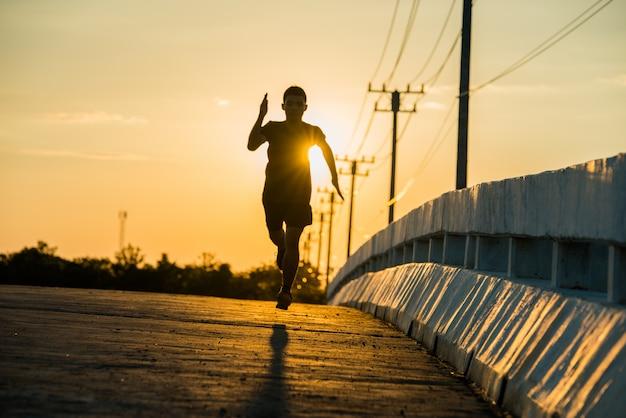 Силуэт молодого человека фитнес работает на рассвете Бесплатные Фотографии