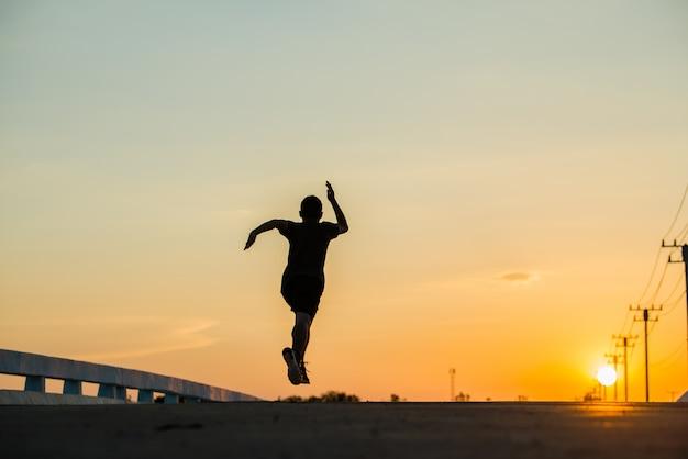 日の出を走っている若いフィットネス男のシルエット 無料写真