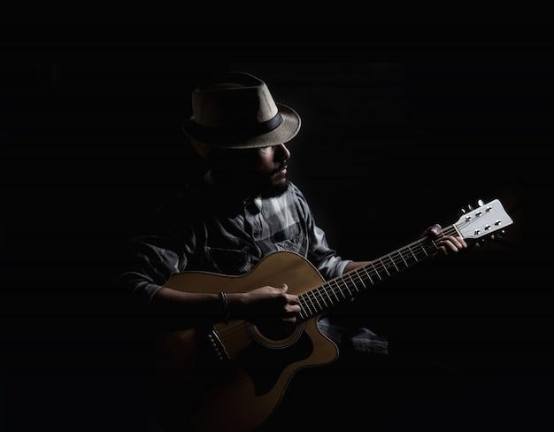 ヤングヒップスターのギタリストは、アコースティックギターで遊ぶ。 無料写真